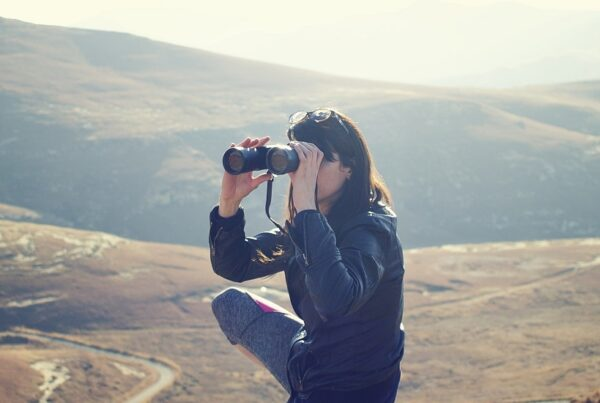 woman on a mountain with binoculars